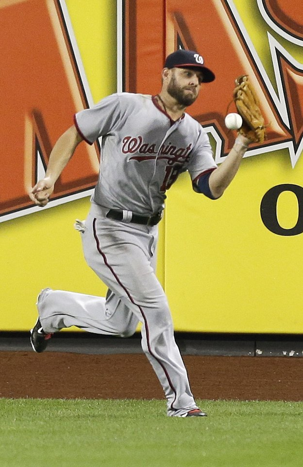 Photo - Washington Nationals left fielder Kevin Frandsen drops a ball hit by New York Mets' Travis d'Arnaud for an error during the fourth inning of a baseball game Wednesday, Aug. 13, 2014, in New York. New York Mets' Lucas Duda scored on the play. (AP Photo/Frank Franklin II)