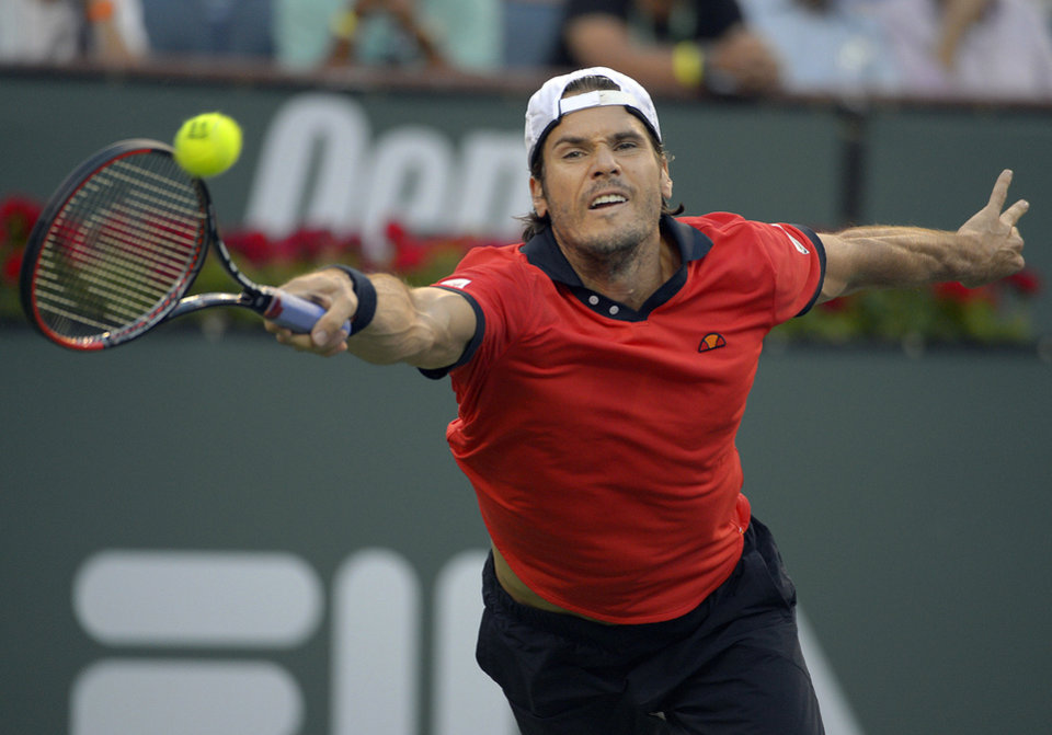 Photo - Tommy Haas, of Germany, reaches for the ball against Roger Federer, of Switzerland, during a fourth-round match at the BNP Paribas Open tennis tournament on Wednesday, March 12, 2014, in Indian Wells, Calif. (AP Photo/Mark J. Terrill)