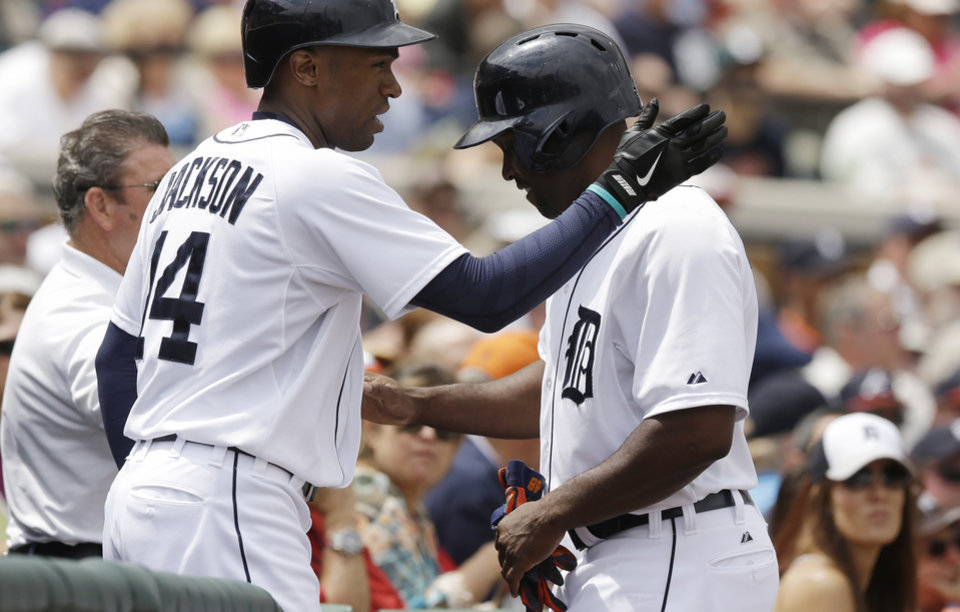 Photo - Detroit Tigers' Torii Hunter, right, is congratulated by Austin Jackson after scoring in the first inning on a sacrifice by teammate Victor Martinez in a spring exhibition baseball game against the Atlanta Braves in Lakeland, Fla., Tuesday, March 25, 2014. (AP Photo/Carlos Osorio)