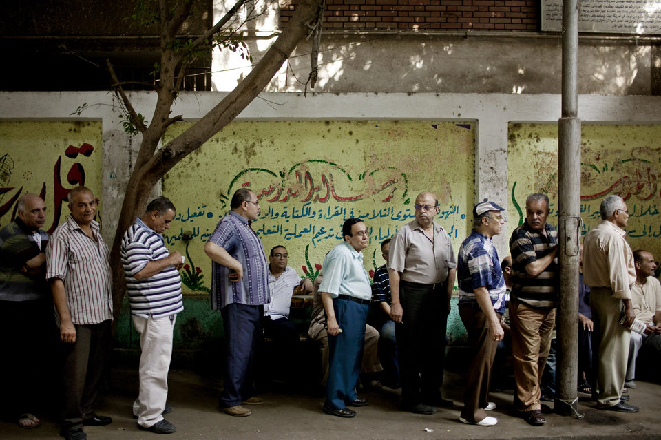 Photo -   Egyptian men line up to vote at a polling station in the Shobra neighborhood of Cairo, Egypt on Sunday, June 17, 2012. Egyptians are choosing on Sunday between a conservative Islamist and Hosni Mubarak's ex-prime minister in the second day of a presidential runoff that has been overshadowed by questions on whether the ruling military will transfer power to civilian authority by July 1 as promised. (AP Photo/Pete Muller)