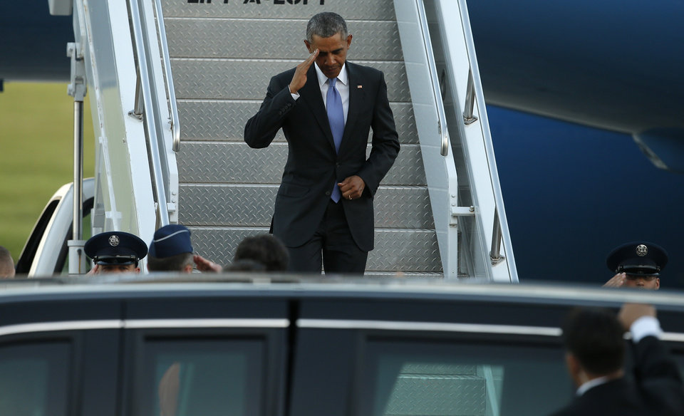 Photo - President Barack Obama salutes as he exits Air Force One at Tinker Air Force Base in Midwest City, Wednesday, July 15, 2015. President Barack Obama will visit the Federal Correctional Institution El Reno, where he will meet with Oklahoma law enforcement officials and inmates and conduct an interview for a documentary scheduled to air in the fall. Photo by Bryan Terry, The Oklahoman