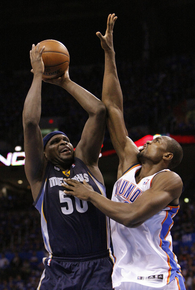 Photo - Memphis Grizzlies Zach Randolph, left, shoots as Oklahoma City Thunder's Serge Ibaka defends during the fourth quarter of Game 1 of their Western Conference Semifinals NBA basketball playoff series in Oklahoma City, Sunday, May 5, 2013.  Oklahoma City won 93-91. (AP Photo/Alonzo Adams)