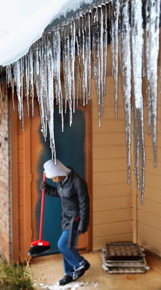 Photo -   A woman, who only would  gave her name as Florence, knocks snow from her shoes as she stands beneath a curtain of icicles after clearing snow from  her car at her Del City apartment on Tyanne Blvd., Jan. 30, 2010.  Photo by Jim Beckel, The Oklahoman