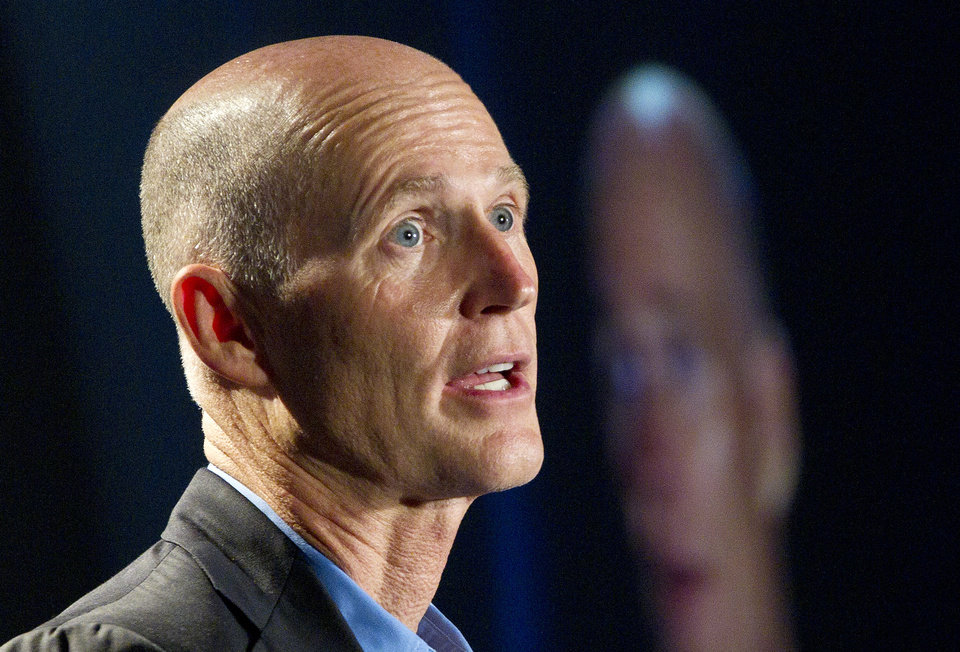 Photo -   FILE - In this May 16, 2012 file photo, Florida Gov. Rick Scott speaks in Fort Lauderdale, Fla. From the South to the heartland, cracks are appearing in the once-solid wall of Republican resistance to President Barack Obama's health care law. Gov. Scott, one of the most visible opponents of Obama's overhaul, now says