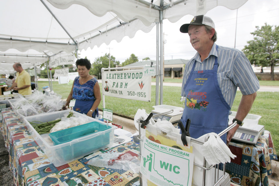 Photo - BUD LEATHERWOOD: Bud and Lita Leatherwood of Yukon, post a sign that his stand is approved for WIC sales at the Farmers Market at NW 63rd and Western in Oklahoma City, Oklahoma August 27, 2009. Photo by Steve Gooch, The Oklahoman ORG XMIT: KOD