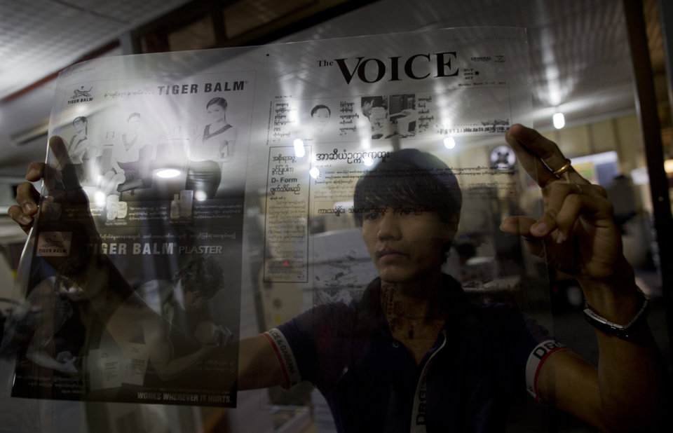"In this March 15, 2013 photo, a printing worker of weekly journal ""The Voice,"" inspects a sheet-film, that use for printing in a printing press in Yangon, Myanmar. The Voice Weekly news journal was temporarily suspended for 6-times during the period of 2005-2012. After eight months and 26 hearings, Myanmar's ministry of mining dropped its controversial defamation lawsuit against the journal in early 2013. The lawsuit originated from publication of corruption allegations against the ministry in 2012.  Myanmar's newly energized press corps is calling on the government to revise a proposed new publishing law, saying it will mark a severe setback to press freedoms and replace the country's old censorship regime with other forms of repression. (AP Photo/Gemunu Amarasinghe)"