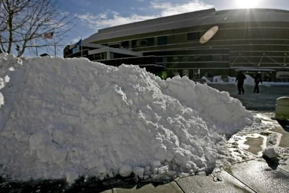 Photo - People walk past a pile of snow on the way to the Oklahoma City Arena on Wednesday, Feb. 2, 2011. Photo by Bryan Terry
