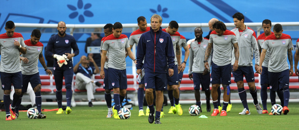 United States\' Jurgen Klinsmann, center, walks on the pitch with his team during a training session at the Arena da Amazonia in Manaus, Brazil, Sunday, June 22, 2014. The U.S. will play Portugal in group G of the 2014 soccer World Cup on June 22. (AP Photo/Paulo Duarte)