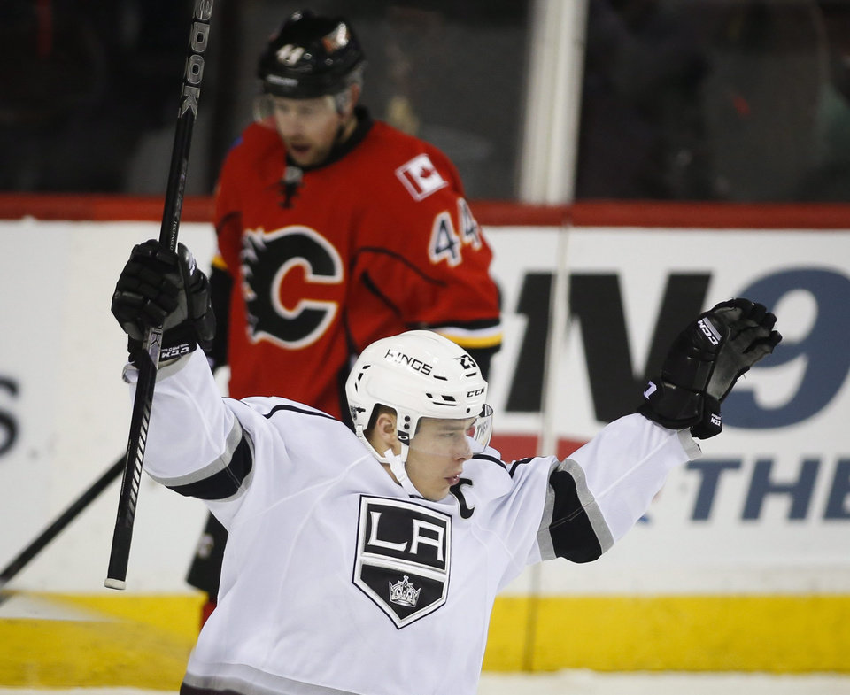 Photo - Los Angeles Kings' Dustin Brown celebrates his goal as Calgary Flames' Chris Butler skates away during the first period of an NHL hockey game Thursday, Feb. 27, 2014, in Calgary, Alberta. (AP Photo/The Canadian Press, Jeff McIntosh)