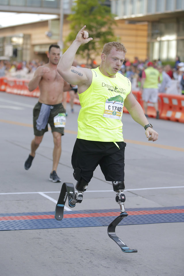 Photo - Trevor Bunch finishes the half marathon during the Oklahoma City Memorial Marathon in Oklahoma City, Sunday, April 28, 2019. [Bryan Terry/The Oklahoman]