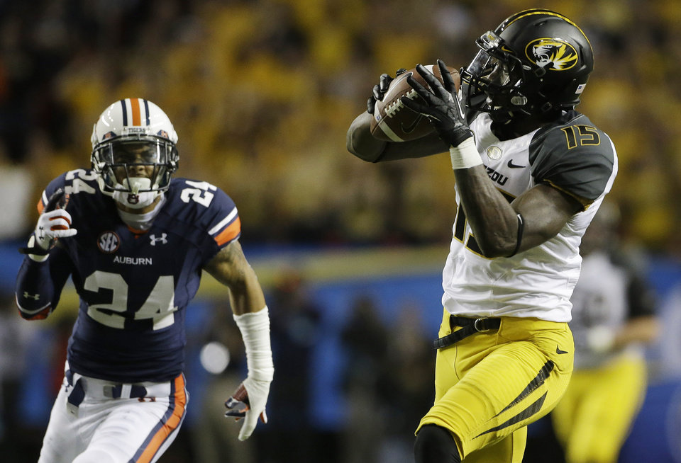 Photo - Missouri wide receiver Dorial Green-Beckham (15) prepares to run into the end zone against Auburn defensive back Jermaine Whitehead (9) during the first half of the Southeastern Conference NCAA football championship game, Saturday, Dec. 7, 2013, in Atlanta. (AP Photo/John Bazemore)