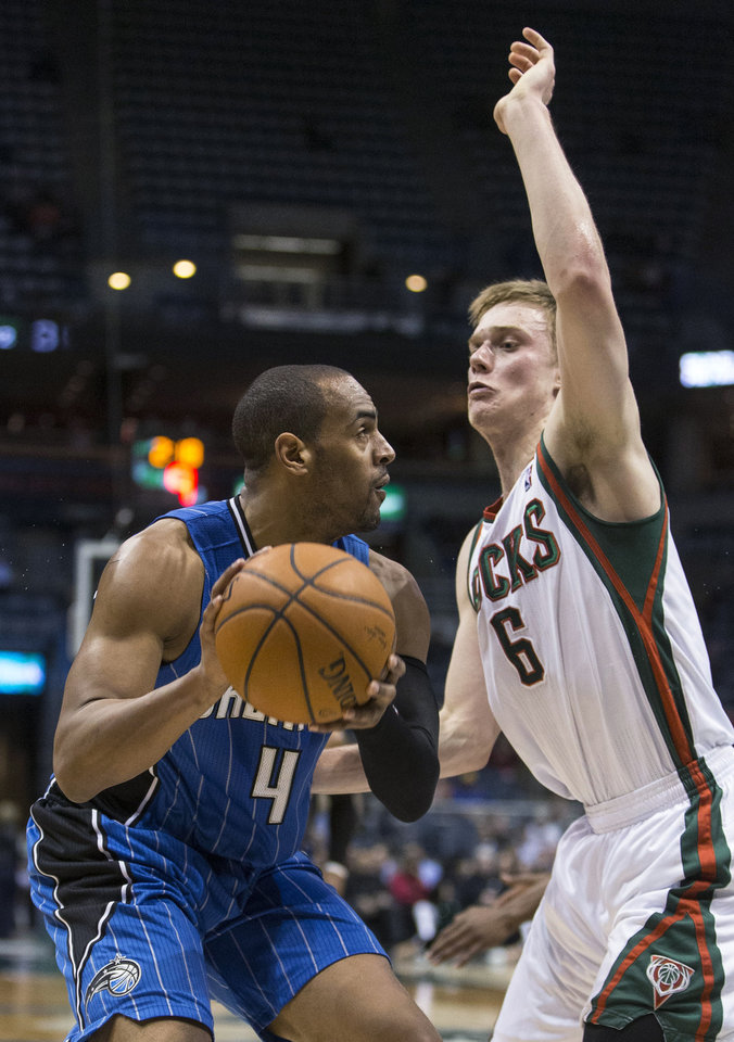 Photo - Milwaukee Bucks' Nate Wolters stops the drive of Orlando Magic's Arron Afflalo during the first half of an NBA basketball game Tuesday, Feb. 18, 2014, in Milwaukee. (AP Photo/Tom Lynn)