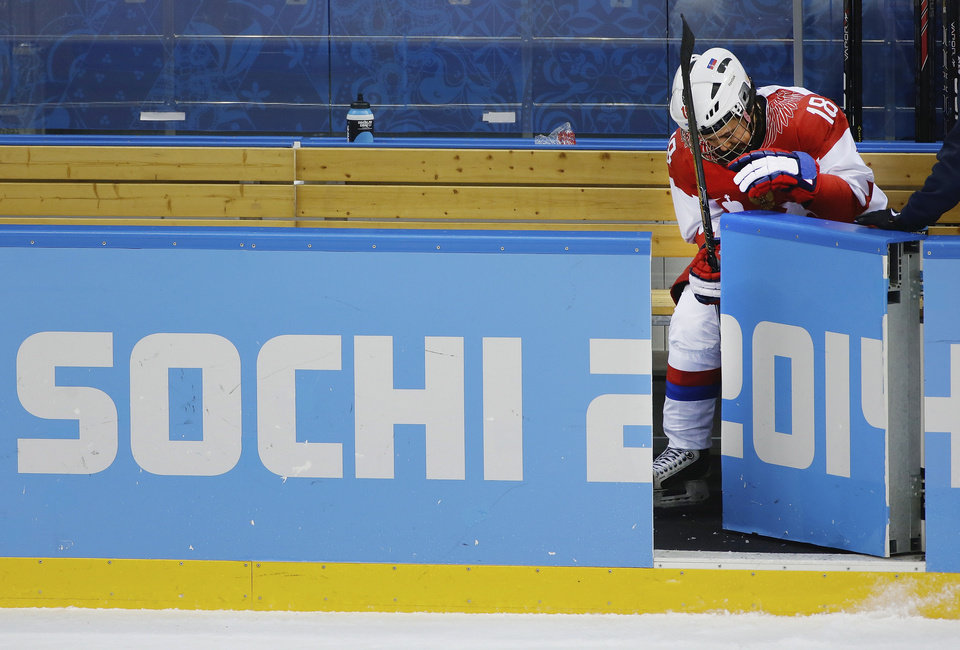 Photo - Olga Sosina of Russia sits on the bench after Russia's 2-0 loss to Swtizerland during the 2014 Winter Olympics women's ice hockey quarterfinal game at Shayba Arena, Saturday, Feb. 15, 2014, in Sochi, Russia. (AP Photo/Matt Slocum)