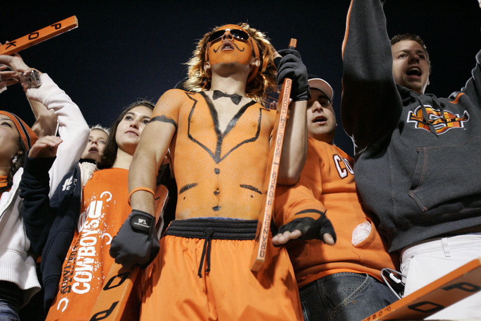 Photo - Oklahoma State fans wear their formal body paint during the second half of the college football game between Oklahoma State University (OSU) and the University of Missouri (MU) at Boone Pickens Stadium in Stillwater, Okla. Saturday, Oct. 17, 2009.  Photo by Steve Sisney, The Oklahoman