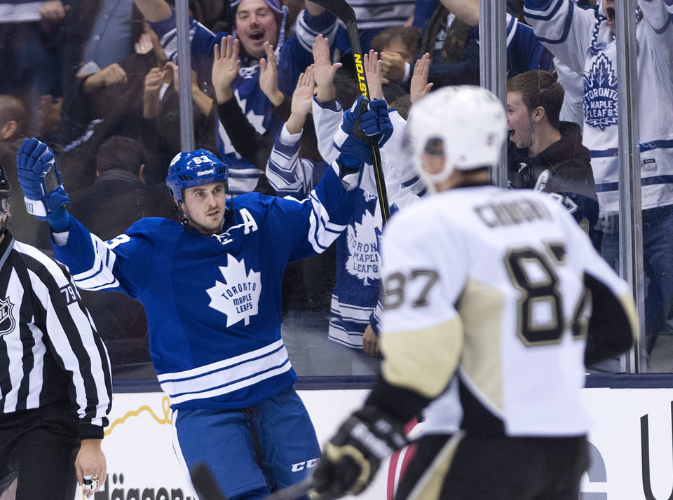 Photo - Toronto Maple Leafs forward Dave Bolland, left, celebrates his short handed goal as Pittsburgh Penguins captain Sidney Crosby, right, looks on during the first period of an NHL hockey game, Saturday, Oct. 26, 2013 in Toronto. (AP Photo/The Canadian Press, Nathan Denette)