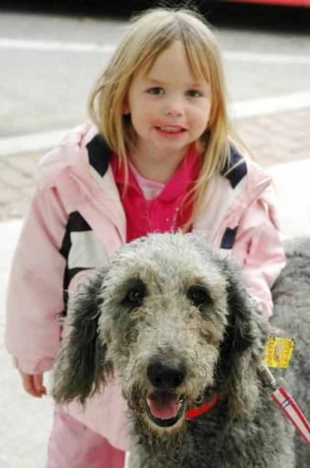 Photo - Brianna Tyler, 3, of Blanchard with her family's new Labradoodle adopted Thursday, Oct. 22, 2009. The  dog was one of more than 90 rescued from a  Pottawatomie County puppy mill this week. Photo by Ann Kelley, The Oklahoman