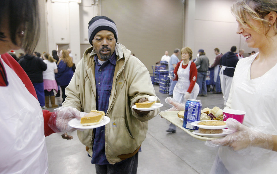 Photo - Steve (did not want to give his last name) is offered pumpkin pie by volunteers in the dessert area at the annual Red Andrews Christmas Dinner at the Cox Convention Center in downtown Oklahoma City, Thursday, Dec. 25, 2008. Volunteer Ashley Webb, right, carried  his tray through the serving line and then helped him find a place to sit. This is Webb's second year to volunteer at the dinner.     BY JIM BECKEL, THE OKLAHOMAN ORG XMIT: KOD