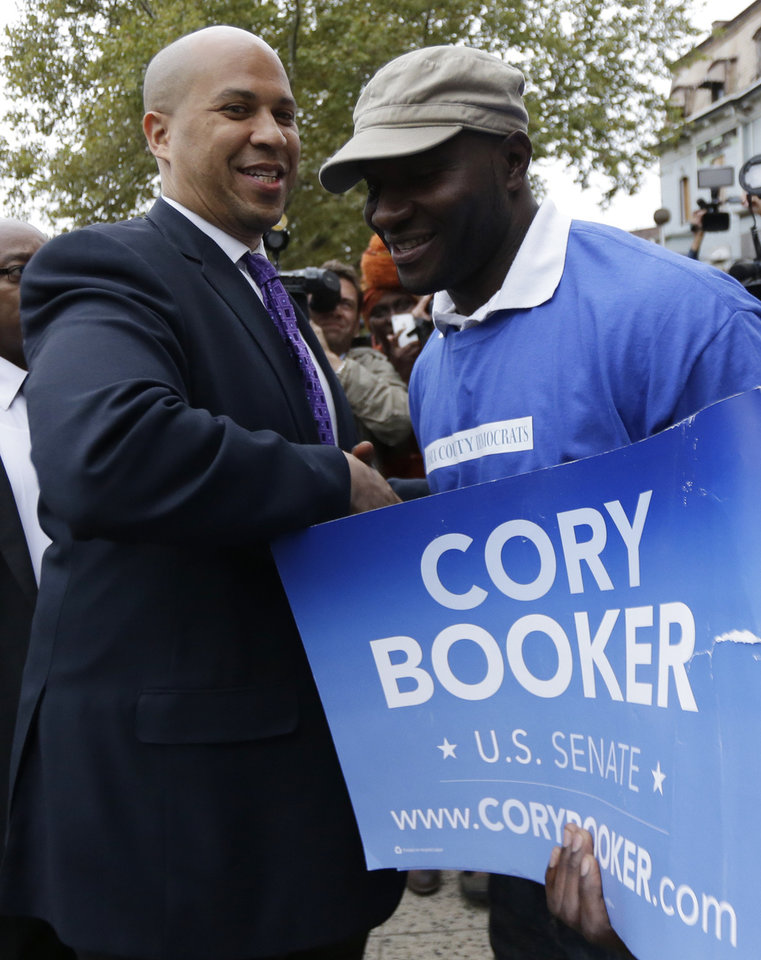 Photo - Newark Mayor Cory Booker, left, is greeted by Dosso Kassimou outside of a polling place before casting his vote in a special election for the vacant New Jersey seat in the U.S. Senate, Wednesday, Oct. 16, 2013, in Newark, N.J. Booker is going up against Republican Steve Lonegan. (AP Photo/Julio Cortez)