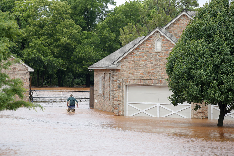 Photo - A man walks through floodwaters by a home on Council just north of NW 164 in Oklahoma City, Tuesday, May 21, 2019. [Bryan Terry/The Oklahoman]