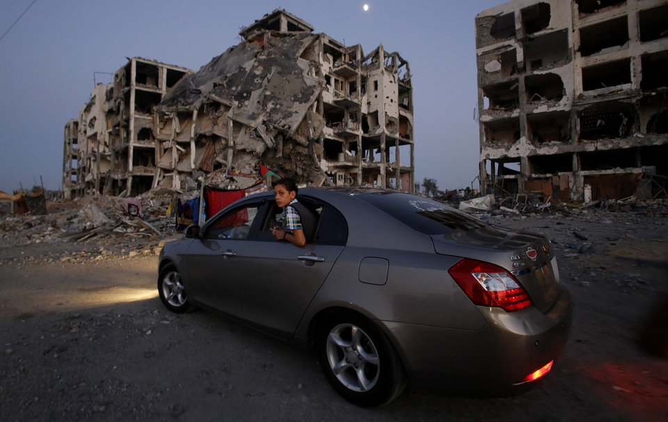 Photo - A Palestinian boy surveys the destruction of buildings at a residential neighborhood, in Beit Lahiya, northern Gaza Strip, Thursday, Aug. 7, 2014. Hamas held on Thursday its first public rally since a cease-fire with Israel, with Hamas official Mushir al-Masri, vowing the militant group would never give up its arms and will continue to fight until the Gaza Strip blockade is lifted. (AP Photo/Hatem Moussa)