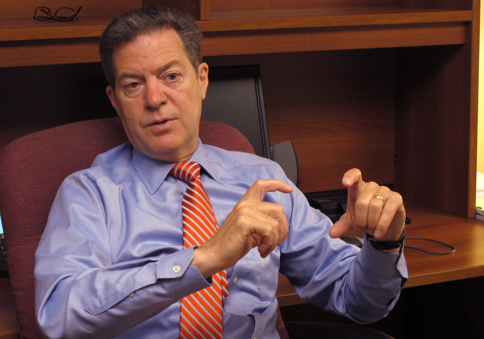 Photo - Kansas Gov. Sam Brownback answers questions for reporters during an impromptu visit to The Associated Press office at the Statehouse, Wednesday, July 23, 2014, in Topeka, Kan. Brownback called on wind-energy advocates and opponents of a renewable-energy rule to compromise on the policy's future. (AP Photo/Credit withheld)