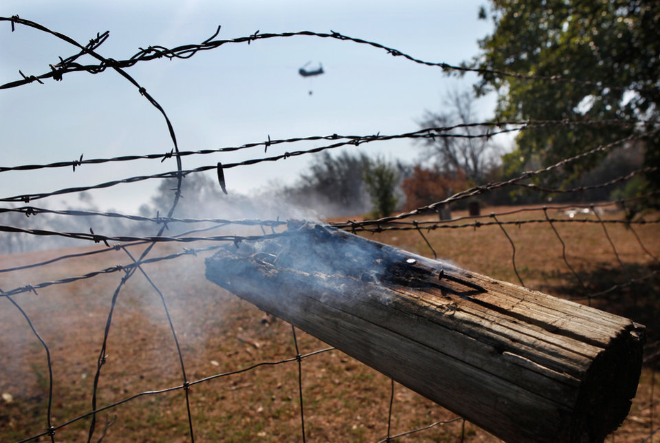 Photo - A section of a fence post smolders Wednesday after wildfires ravaged land and property that stretched from NE 50 on the south to Hefner Road on the north.  The fire extended from Sooner Road to Midwest Blvd.  A military helicopter carrying water to be dumped on the fire can be seen in the background.   Photo taken Wednesday, Aug. 31, 2011. Photo by Jim Beckel, The Oklahoman