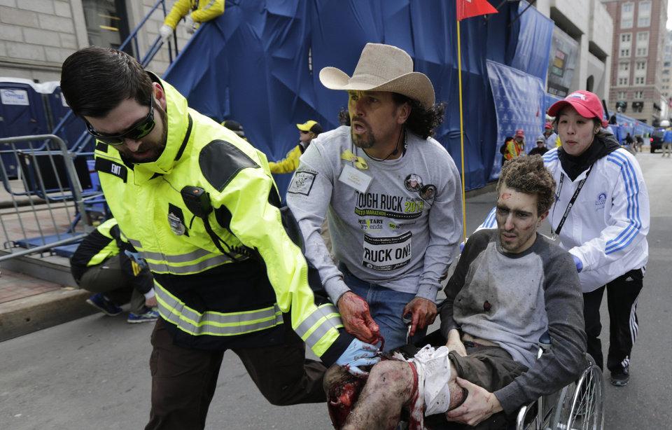 Medical responders run an injured man past the finish line the 2013 Boston Marathon following an explosion in Boston, Monday, April 15, 2013. Two explosions shattered the euphoria of the Boston Marathon finish line on Monday, sending authorities out on the course to carry off the injured while the stragglers were rerouted away from the smoking site of the blasts. (AP Photo/Charles Krupa) ORG XMIT: MACK118