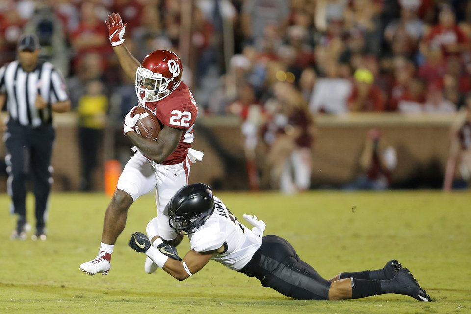 Photo - Oklahoma's T.J. Pledger (22) carries the ball past Army's Jaylon McClinton (7) during a college football game between the University of Oklahoma Sooners (OU) and the Army Black Knights at Gaylord Family-Oklahoma Memorial Stadium in Norman, Okla., Saturday, Sept. 22, 2018. Photo by Bryan Terry, The Oklahoman