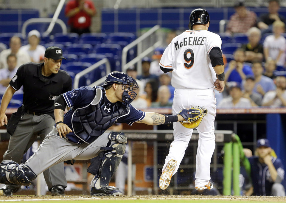 Photo - San Diego Padres catcher Yasmani Grandal, center, is unable to tag Miami Marlins' Casey McGehee (9) who scores on a double by Garrett Jones during the fifth inning of a baseball game on Friday, April 4, 2014, in Miami. (AP Photo/Wilfredo Lee)