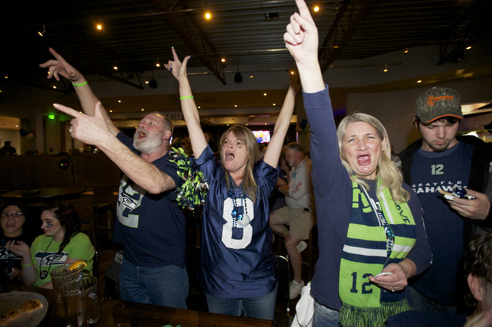 Photo - Seahawks fans from left, Ron Taylor, Michelle Taylor and Vienna Creighton celebrate while watching Super Bowl XLVIII at Big Al's in Vancouver, Wash., Sunday, Feb. 2, 2014. Seattle defeated the Denver Broncos 43-8. (AP Photo/The Columbian, Steven Lane)