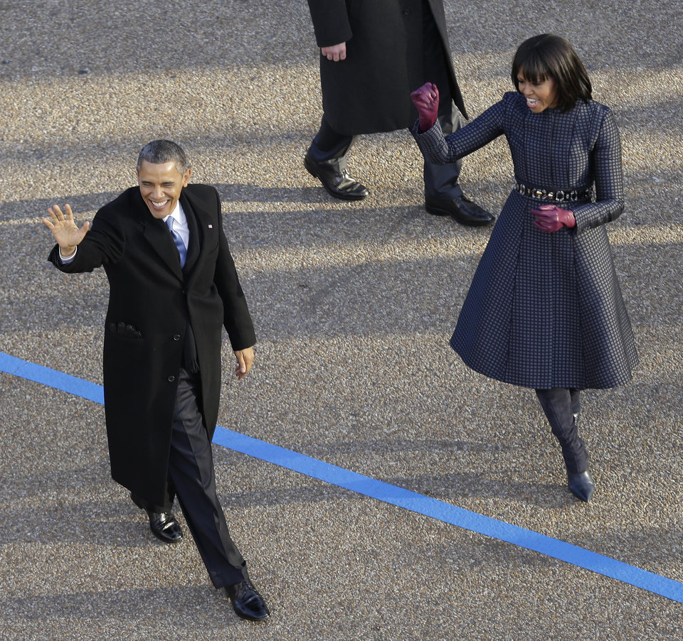 President Barack Obama and first lady Michelle Obama walk the inaugural parade route down Pennsylvania Avenue en route to the White House, Monday, Jan. 21, 2013, in Washington. Thousands marched during the 57th Presidential Inauguration parade after the ceremonial swearing-in of President Barack Obama. (AP Photo/Charlie Neibergall) ORG XMIT: DCMS110