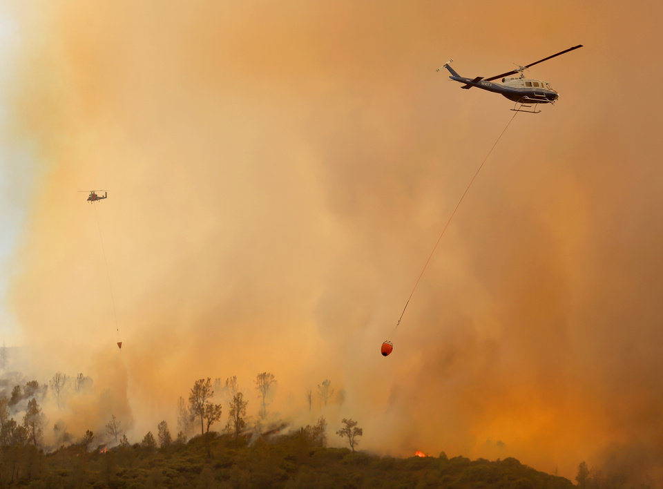 Private hire helicopters make water drops on the Butts Fire above Snell Valley as the afternoon winds kicked up, Wednesday, July 2, 2014, near Middletown, Calif. (AP Photo/Santa Rosa Press Democrat, Kent Porter)