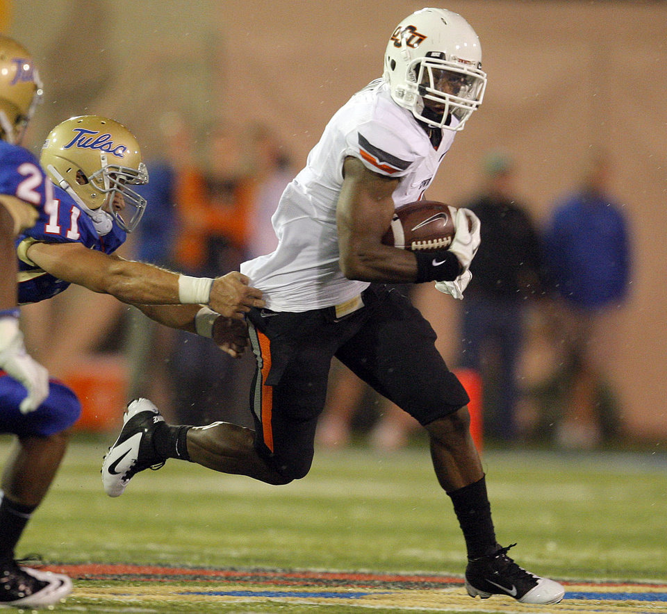 Photo - Tulsa's Alan Dock (11) tries to bring down Oklahoma State's Joseph Randle (1) during a college football game between the Oklahoma State University Cowboys and the University of Tulsa Golden Hurricane at H.A. Chapman Stadium in Tulsa, Okla., Sunday, Sept. 18, 2011. Photo by Sarah Phipps, The Oklahoman