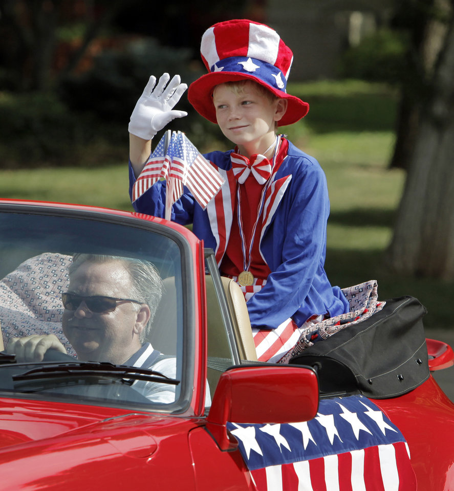 Brevin Senner, 11, waves as he is driven by Mike McAuliffe along Quail Creek Road during the Quail Creek Fourth of July parade in Oklahoma City, Saturday, July 4, 2009. Photo by Nate Billings, The Oklahoman