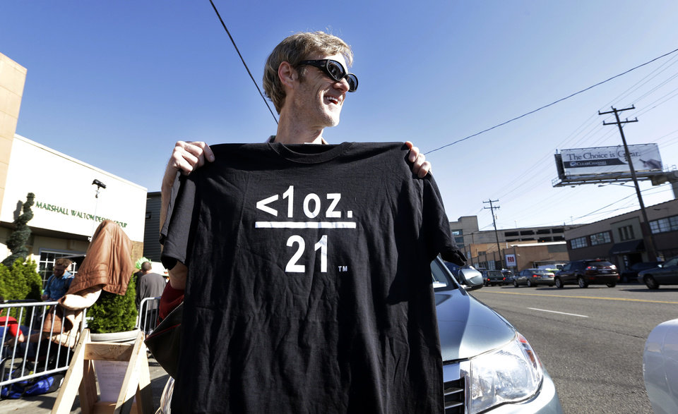 Photo - Terry Martin displays a tee shirt he's selling celebrating legal marijuana in front of Cannabis City, as he waits with others on the first day that sales of recreational pot is legal in the state Tuesday, July 8, 2014, in Seattle. The symbols translate that under one ounce of pot and over 21-years of age means that it's legal. The shop is the first and, initially, only store in Seattle to legally sell pot. (AP Photo/Elaine Thompson)