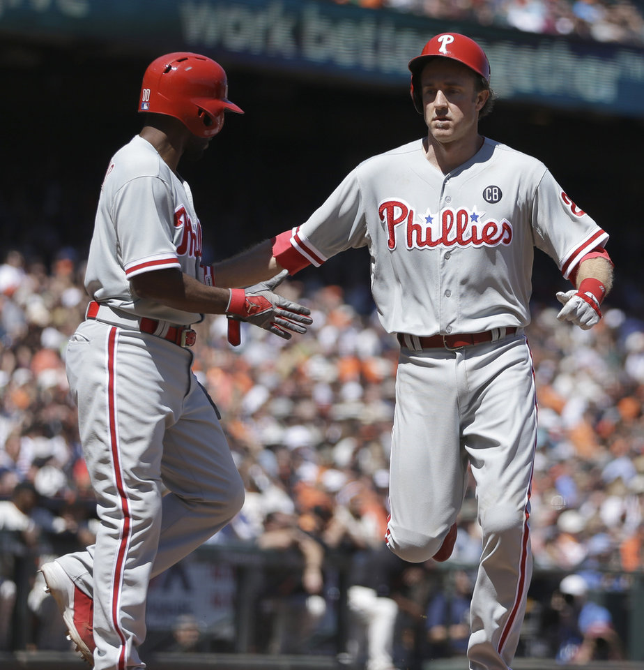 Photo - Philadelphia Phillies' Jimmy Rollins, left, and Chase Utley celebrate after scoring against the San Francisco Giants in the fifth inning of a baseball game Saturday, Aug. 16, 2014, in San Francisco. Both scored on a single by Phillies' Ryan Howard. (AP Photo/Ben Margot)