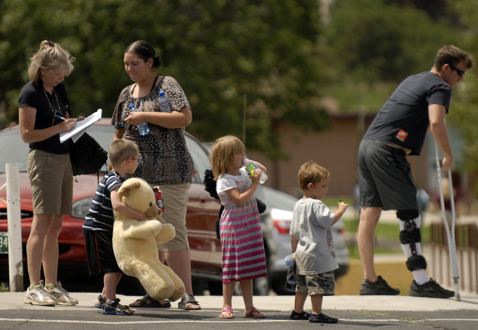 Photo -   Evacuees of the Waldo Canyon Fire are assisted by a volunteers from the Red Cross at the Cheyenne Mountain High School evacuation center on Wednesday, June 27, 2012, in Colorado Springs, Colo. The wildfire doubled in size overnight to about 24 square miles (62 square kilometers), and has so far forced mandatory evacuations for more than 32,000 residents. (AP Photo/Bryan Oller)