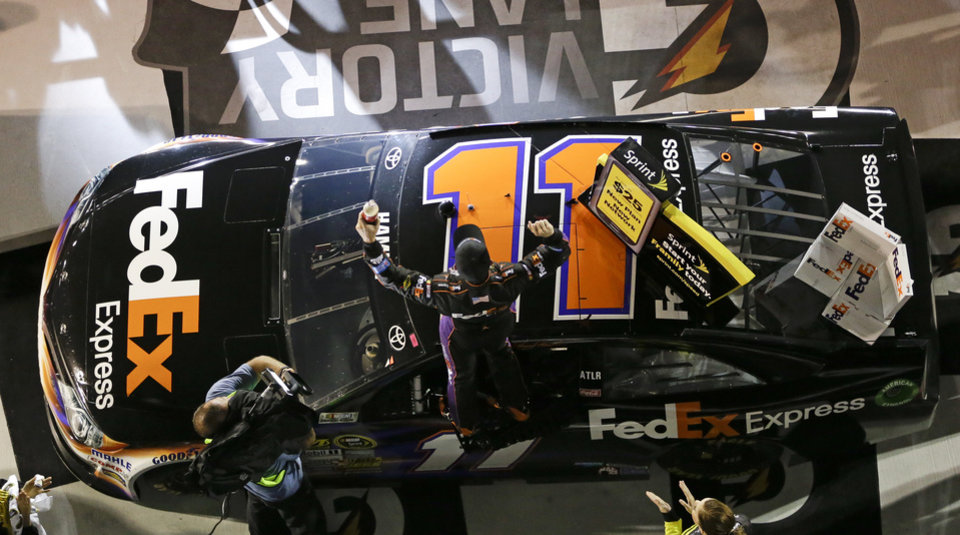 Photo - Denny Hamlin, center, cheers as he stands on his car in Victory Lane after winning the second of two NASCAR Sprint Cup qualifying auto races at Daytona International Speedway in Daytona Beach, Fla., Thursday, Feb. 20, 2014. (AP Photo/John Raoux)