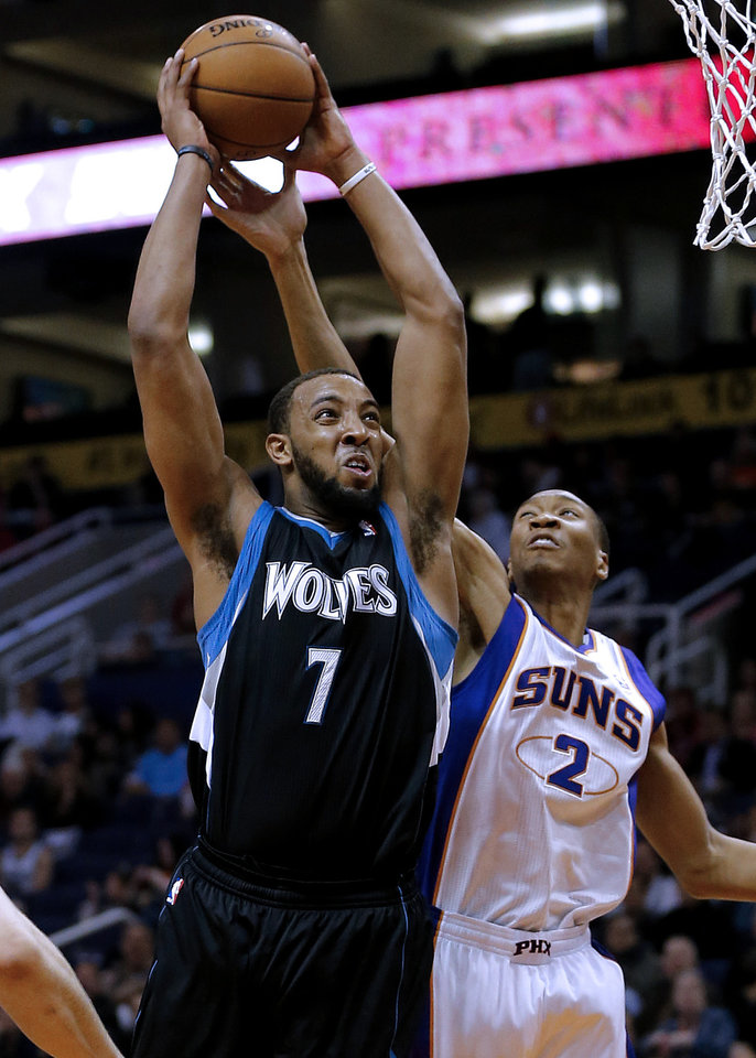 Minnesota Timberwolves' Derrick Williams (7) dunks over Phoenix Suns' Wesley Johnson (2) during the first half of an NBA basketball game, Tuesday, Feb. 26, 2013, in Phoenix. (AP Photo/Matt York)