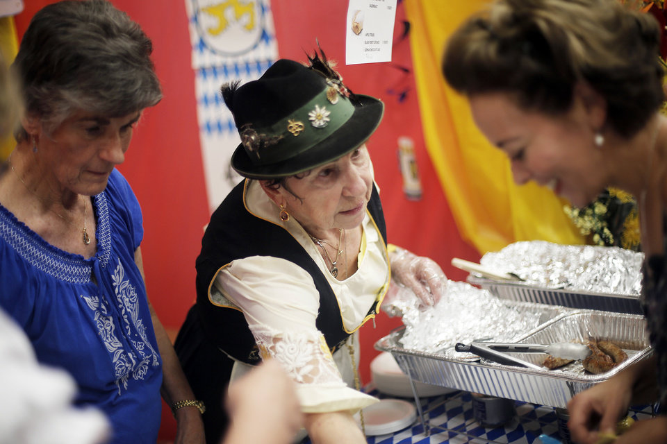 Photo - Hilde Effinger (center), of Yukon, serves up German food during a multicultural food festival at St. Eugene Catholic Church in Oklahoma City, Sunday, Sept. 9, 2012.  Photo by Garett Fisbeck, The Oklahoman  Garett Fisbeck - Garett Fisbeck
