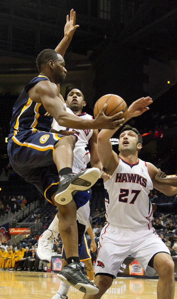 Indiana Pacers small forward Sam Young, left, drives around Atlanta Hawks' Al Horford (15) and Zaza Pachulia (27) in the first half of an NBA basketball game on Wednesday, Nov. 7, 2012, in Atlanta. (AP Photo/John Bazemore)