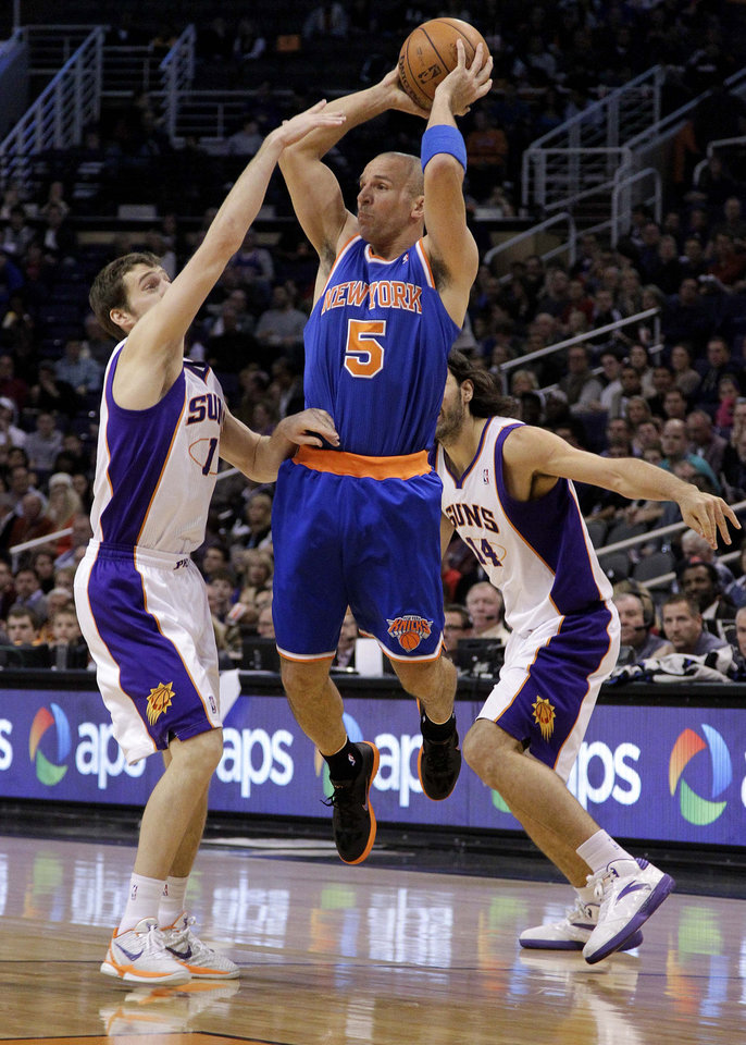 Photo - New York Knicks guard Jason Kidd (5) passes over Phoenix Suns' Goran Dragic, of Slovenia, (1), and Luis Scola, of Argentina, during the first half of an NBA basketball game on Wednesday, Dec. 26, 2012, in Phoenix. (AP Photo/Matt York)