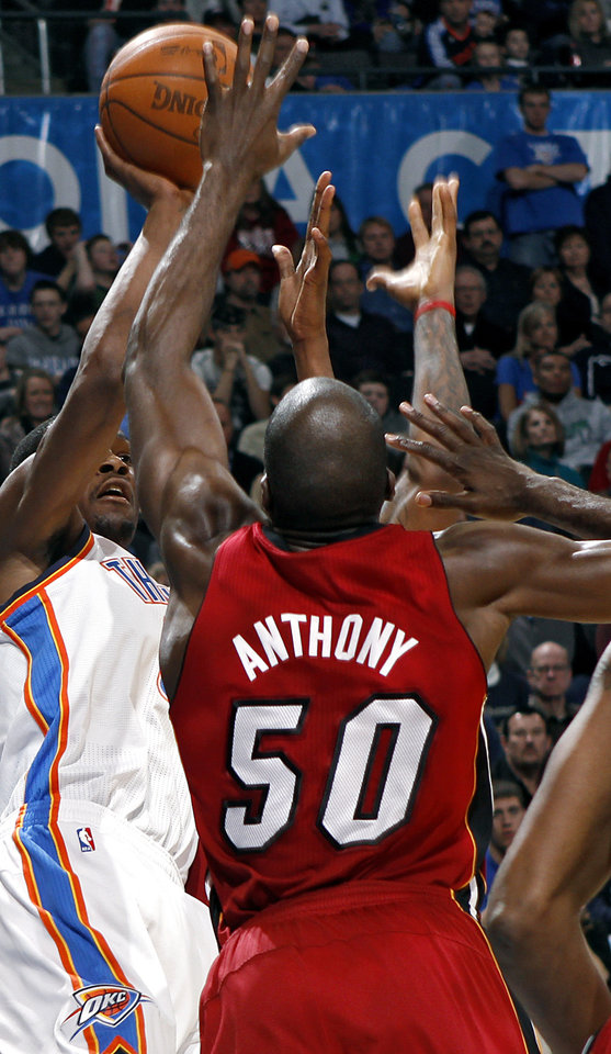 Photo - Oklahoma City's Kevin Durant gets off a shot in front of Miami's Joel Anthony during their NBA basketball game at the OKC Arena in Oklahoma City on Thursday, Jan. 30, 2011. The Heat beat the Thunder 108-103. Photo by John Clanton, The Oklahoman