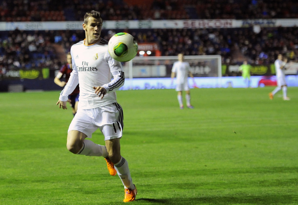 Photo - Real Madrid's Gareth Bale of Wales goes for the ball during their Spanish Copa del Rey round-16 second leg soccer match between Osasuna and Real Madrid , at El Sadar stadium, in Pamplona northern Spain on Wednesday, Jan. 15, 2014. (AP Photo/Alvaro Barrientos)