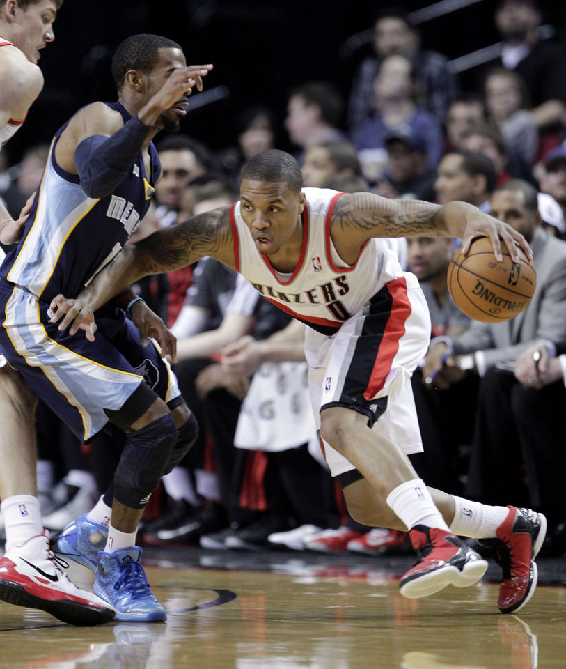 Photo - Portland Trail Blazers guard Damian Lillard, right, drives on Memphis Grizzlies guard Mike Conley during the first quarter of an NBA basketball game in Portland, Ore., Wednesday, April 3, 2013.(AP Photo/Don Ryan)