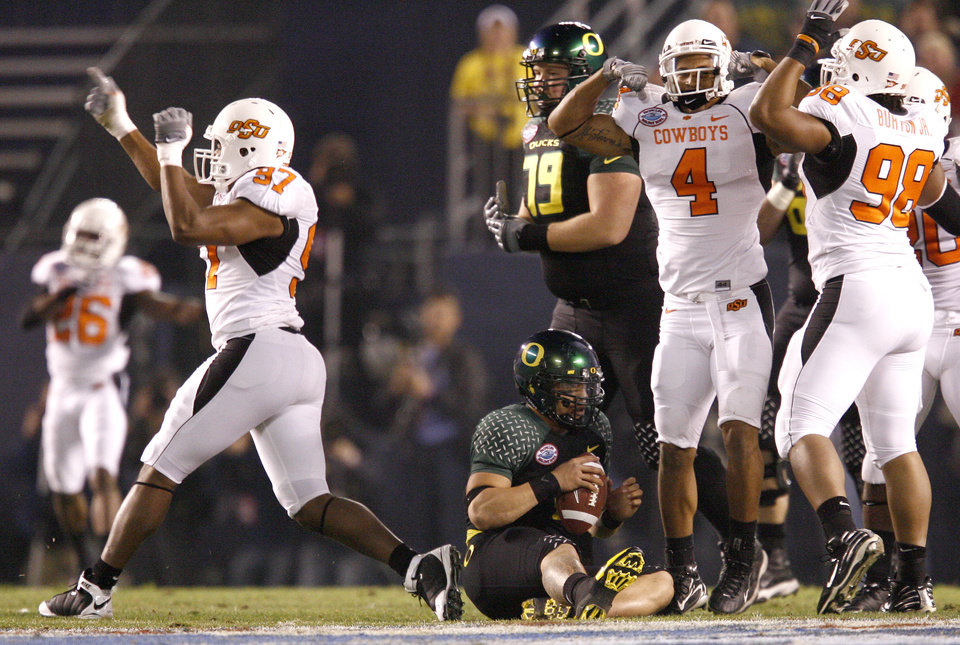 Photo - OSU's Jeremiah Price, left, Patrick Lavine, and Derek Burton celebrate after sacking Oregon's Jeremiah Masoli during the Holiday Bowl college football between Oklahoma State and Oregon at Qualcomm Stadium in San Diego, Tuesday, Dec. 30, 2008.  PHOTO BY BRYAN TERRY, THE OKLAHOMAN.