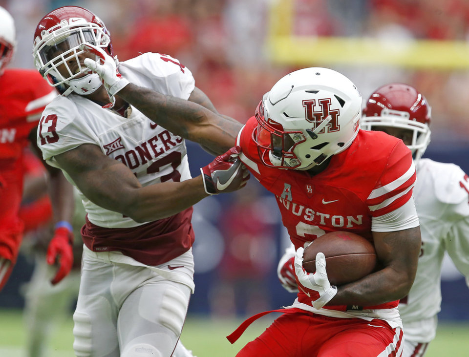 Photo - Houston's Duke Catalon (2) fights off Oklahoma's Ahmad Thomas (13) during the AdvoCare Texas Kickoff college football game between the University of Oklahoma Sooners (OU) and the Houston Cougars at NRG Stadium in Houston, Saturday, Sept. 3, 2016. Houston won 33-23. Photo by Bryan Terry, The Oklahoman