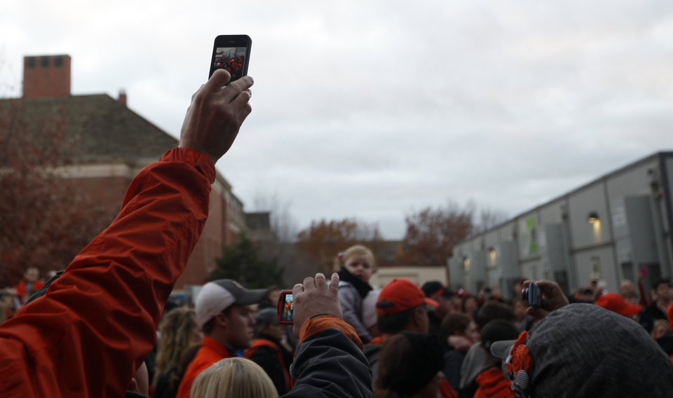 Photo - Fans record the Spirit Walk before the Bedlam college football game between the Oklahoma State University Cowboys (OSU) and the University of Oklahoma Sooners (OU) at Boone Pickens Stadium in Stillwater, Okla., Saturday, Dec. 3, 2011. Photo by Sarah Phipps, The Oklahoman