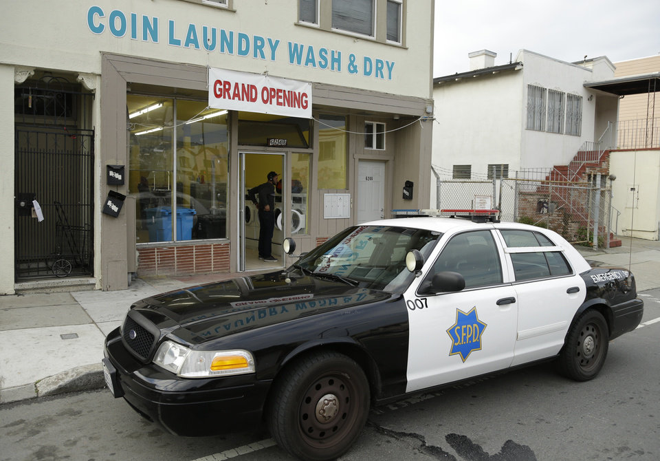 Photo - A San Francisco police car is parked in front of a laundromat where an argument started, which resulted in a woman being set on fire Sunday, Jan. 6, 2013, in San Francisco. San Francisco police say a woman is hospitalized with what are being described as