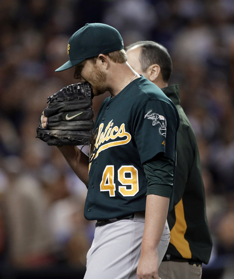 Photo -   Oakland Athletics starting pitcher Brett Anderson (49) bites his glove while walking off the field with a trainer during the third inning of a baseball game against the Detroit Tigers in Detroit, Wednesday, Sept. 19, 2012. (AP Photo/Paul Sancya)